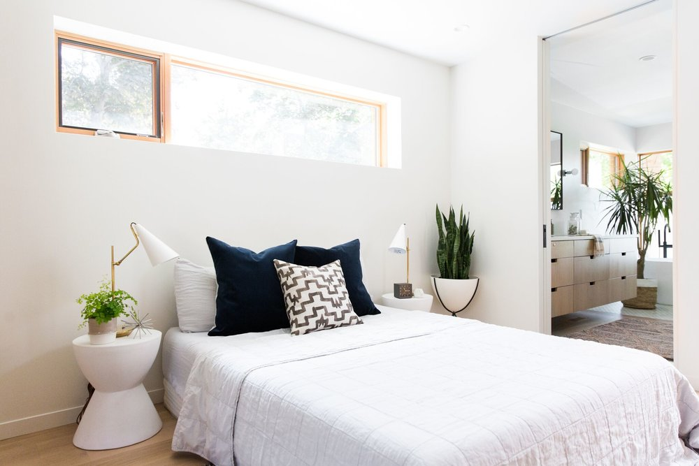 White minimalist bedroom warmed up with natural wood cabinetry