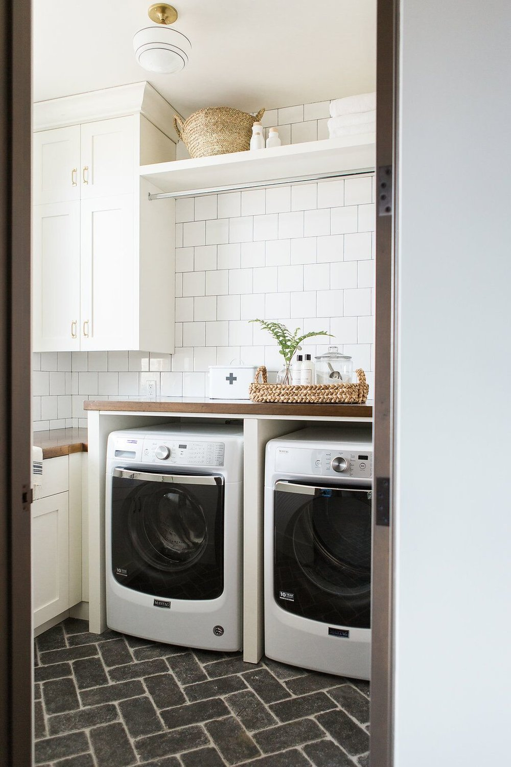 Laundry room with subway tile, cobblestone herringbone floors, and butcher block counter top