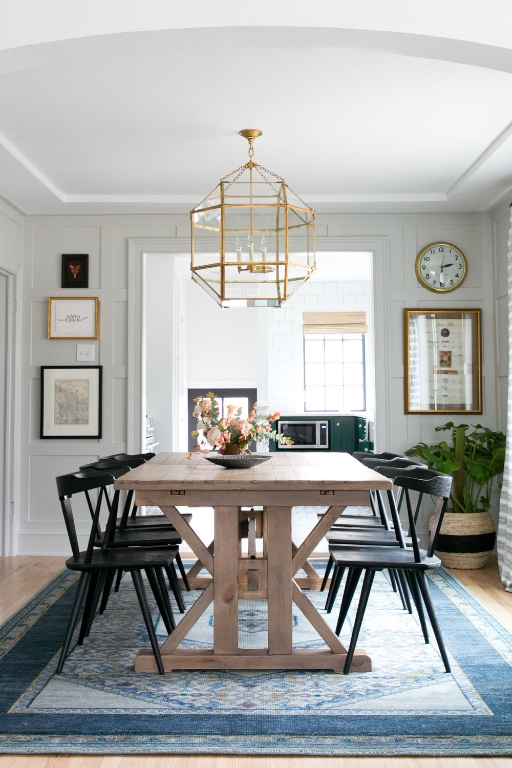 Eclectic dining room with wood dining table, and vintage rug and artwork.